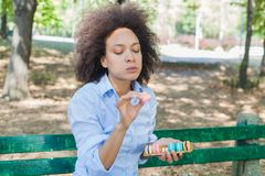 Young African Woman Eating Macarons Cookie In The Park stock image