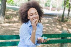 Young African Woman Eating Macarons Cookie In The Park royalty free stock photos