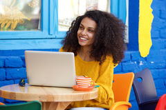 Young african woman enjoying some alone time at cafe. Portrait of young african woman enjoying some alone time at her local coffee shop with laptop on table Royalty Free Stock Images