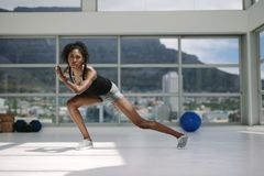 African woman exercising in gym. Young african woman exercising in gym. Female doing stretching workout in health center, standing in a pose Stock Photos