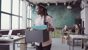 Young african woman getting fired from work. Female walks through the office, carrying box with personal belongings. Young african woman getting fired from work stock footage