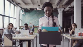 Young african woman getting fired from work. Female walks through the office, carrying box with personal belongings. Young african women getting fired from work Royalty Free Stock Photography