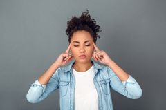Young african woman on grey wall studio casual daily lifestyle relaxed stock photos