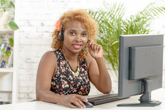 Young African woman with a headset and computer Royalty Free Stock Photography