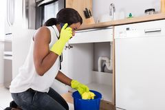 Woman Holding Yellow Napkin Calling Plumber. Young African Woman Holding Yellow Napkin Calling Plumber With Mobile Phone royalty free stock photography