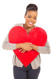 Young african woman hugging red heart shape Stock Photos