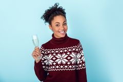 Young african woman isolated on blue wall studio winter concept glass of champagne royalty free stock image