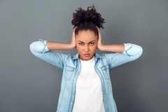 Young african woman isolated on grey wall studio casual daily lifestyle angry stock photo