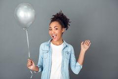 Young african woman isolated on grey wall studio casual daily lifestyle birthday balloon Royalty Free Stock Photos