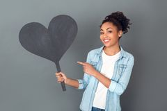 Young african woman isolated on grey wall studio casual daily lifestyle pointing at heart shape Royalty Free Stock Images