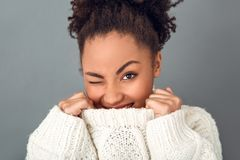 Young african woman isolated on grey wall studio winter concept wink. Young african female wearing woolen sweater isolated on grey wall hiding face in a collar Royalty Free Stock Images