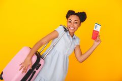 Young african woman isolated on yellow wall studio cute style traveler concept carry luggage Royalty Free Stock Photos
