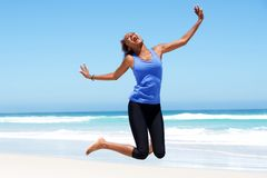 Young african woman jumping with joy at the beach. Portrait of young african woman jumping with joy at the beach royalty free stock photos