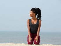 Young african woman kneeling outdoors on beach Royalty Free Stock Photography