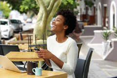 Young african woman laughing with mobile phone at cafe Stock Image
