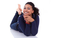 Young African woman lying down on the floor. Portrait of a young African American woman lying down on the floor, isolated on white background Stock Images