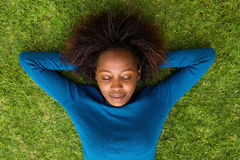 Young african woman lying on grass sleeping Royalty Free Stock Image