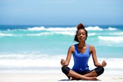 Young african woman meditating in yoga pose at the beach. Portrait of young african american woman meditating in yoga pose outdoors at the beach Royalty Free Stock Photo