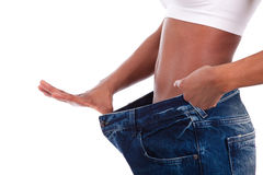 Young african woman in old jeans pant after losing weight. Isolated on white background Stock Images