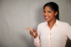 Young african woman pointing while smiling Royalty Free Stock Image