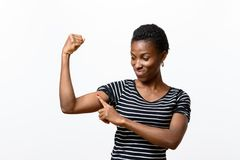 Young African woman pointing to her arm muscles. Slender attractive young African woman pointing to her arm muscles as she flexes her arm with a rueful smile royalty free stock image