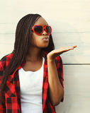 Young african woman in red sunglasses sends an air kis Royalty Free Stock Images