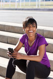 Young african woman relaxing with mobile phone and earphones. Portrait of fit young african woman relaxing with mobile phone and earphones, listening to music Stock Photography