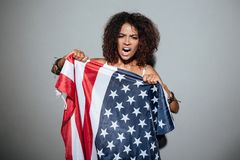 Young african woman screaming. And trying to tear apart USA flag and looking at camera isolated over gray background Royalty Free Stock Images