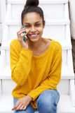 Young african woman sitting on staircase and making phone call Royalty Free Stock Photos