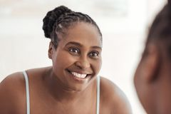 Young African woman smiling at her reflection in a mirror Stock Photos