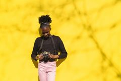 Young african woman smiling and holding camera stock photo