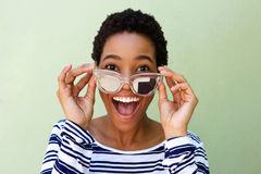 Young african woman smiling with sunglasses against green wall Royalty Free Stock Photo