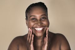 Young African woman smiling and touching her perfect complexion. Smiling young plus size African woman with a perfect complexion standing with her hands on her royalty free stock photo