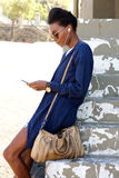 Young african woman standing outdoors using mobile phone Stock Photography