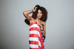 Young african woman standing wrapped in USA flag Royalty Free Stock Images