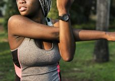 A young African woman stretching in a park Royalty Free Stock Images
