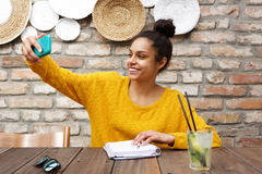 Young african woman taking selfie at cafe Royalty Free Stock Photos