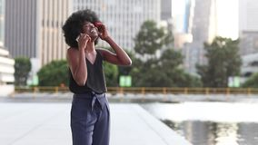 Young african woman talking on the phone while walking by the fountain with a city background skyscrapers. In Los Angeles stock video
