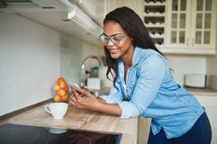 Young African woman texting on a cellphone and drinking coffee. Smiling young African woman leaning on her kitchen counter at home drinking a cup of coffee and royalty free stock photos