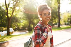 Young african woman walking outdoors in park. Image of amazing young african woman walking outdoors in park. Looking camera Royalty Free Stock Photos
