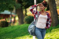 Young african woman walking outdoors in park. Looking aside. Picture of smiling young african woman walking outdoors in park. Looking aside Stock Image