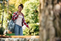 Young african woman walking outdoors in park. Looking aside. Picture of smiling young african woman walking outdoors in park. Looking aside Royalty Free Stock Photography