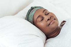 Young African woman wearing a headscarf asleep in bed. Young African woman wearing a headscarf sleeping peacfully in her bed at home in the early morning Stock Photo