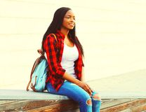 Young african woman wearing a red checkered shirt and backpack. Resting in the city park Stock Photos