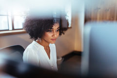 Young african woman working in her office. Shot of young african woman working in her office. Beautiful female executive sitting at her desk looking at computer Royalty Free Stock Image
