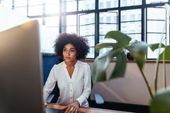 Young african woman working late in office Stock Photo