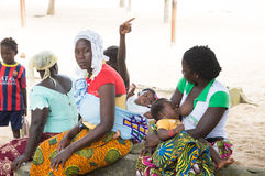 Young African women. Abidjan, ivory coast- August 29,2015: Young African women sitting on a coconut tree trunk in the shade. One breastfeeding her baby, another Stock Photography