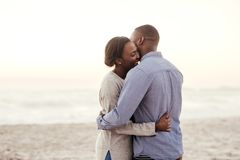 Happy young African couple embracing on a beach at dusk. Young African women standing in her boyfriend`s arms and laughing while enjoying a late afternoon sunset royalty free stock photography