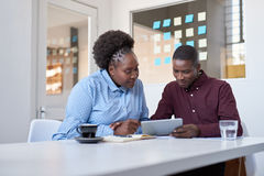 Young African work colleagues using a tablet in an office. Two casually dressed African colleagues looking focused while sitting together at a table in a modern royalty free stock photo