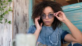 Young Afro American bloger woman speaks by the phone, dreassed in jeans dress, wearing glasses royalty free stock photography